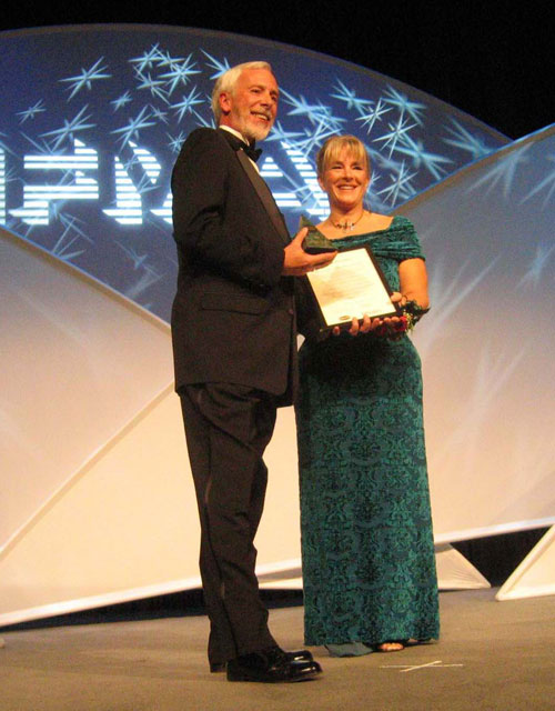Meredith Thatcher on stage being honoured as an IFMA Fellow